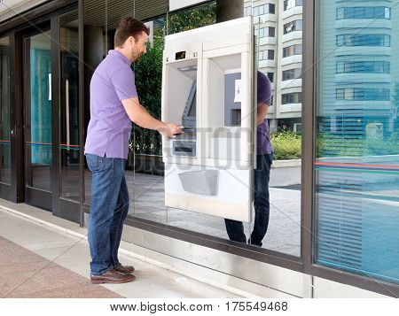 Man Using His Credit Card In An Atm For Withdrawal