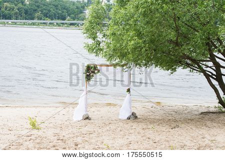 A wedding arch on the river bank with greenery, peonies, and white material.