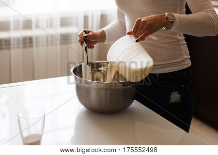 Attractive young woman adding milk to the flour.