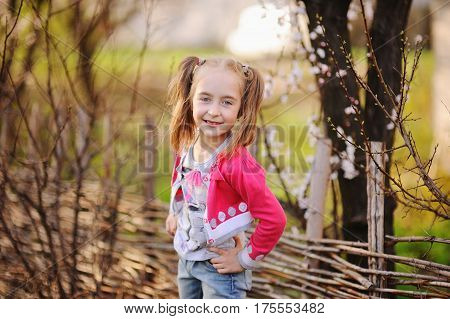 Baby girl without teeth in pink clothes on a background of flowering trees