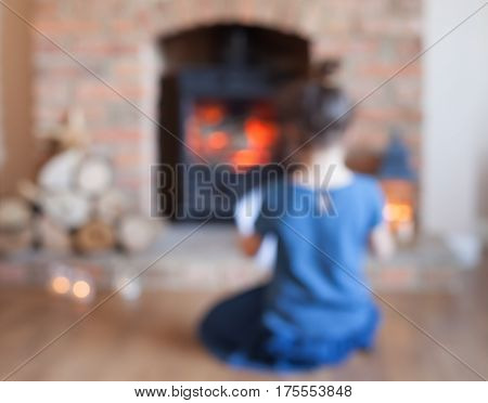 Blurred Background Of Little Girl Sitting In Front Of The Fireplace