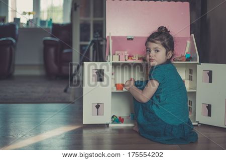 Little Girl Playing With The Dolls House