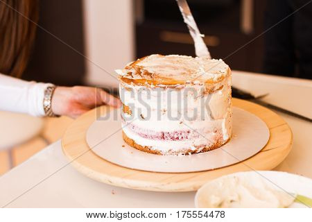 House wife wearing apron making finishing touches on birthday dessert chocolate cake.Woman making homemade cake with easy recipe, sprinkling powdered sugar on top.Icing sugar sprinkled with colander.
