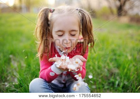 Baby girl blowing off flower petals on background of autumn grass