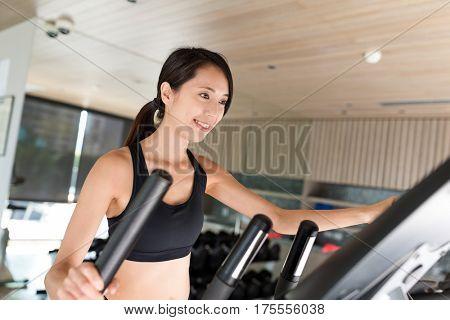 Sport Woman training with Elliptical machine