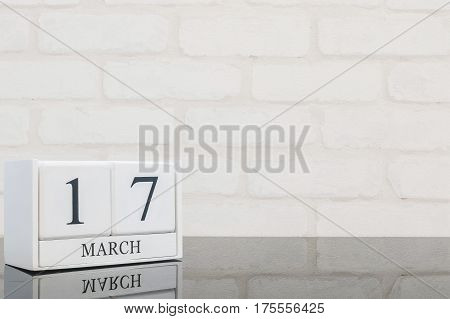 Closeup white wooden calendar with black 17 march word on black glass table and white brick wall textured background with copy space selective focus at the calendar