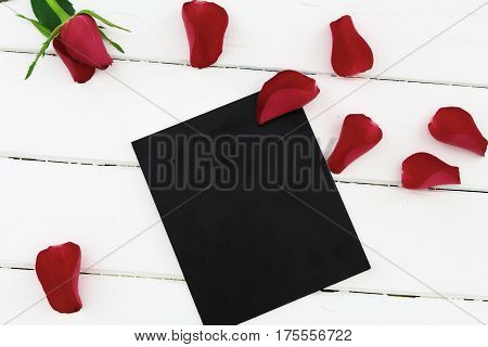 Red rose with greeting card on wood