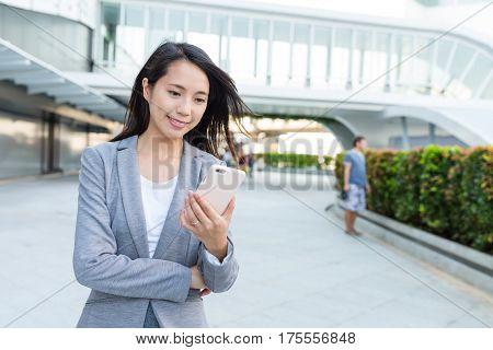 Businesswoman sending sms on cellphone
