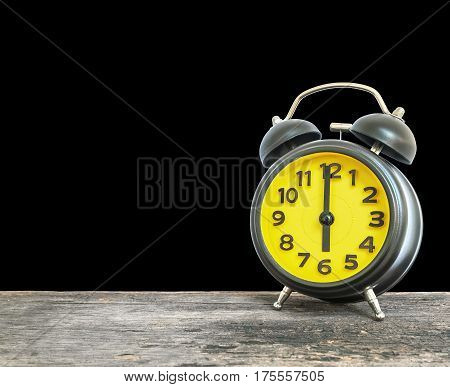 Closeup black and yellow alarm clock for decorate in 6 o'clock on old brown wood desk isolated on black background with copy space