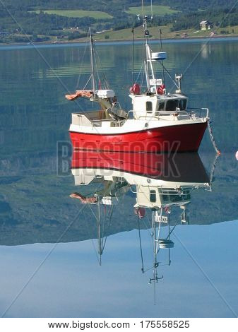 Small fishing boat anchored on the unruffled waters of a Norwegian fjord