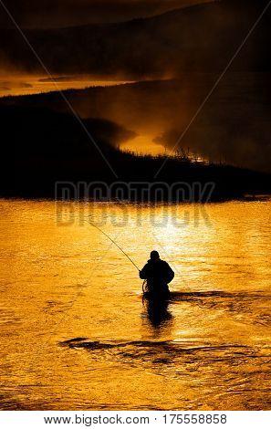 Silhouette of Man Flyfishing Fishing in River