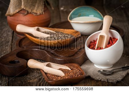 Flax and chia seeds and goji in a wooden spoons on wooden background, healthy superfood