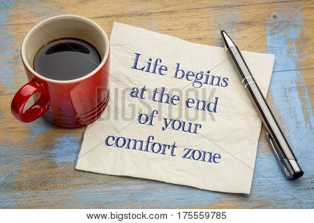 Life begins at the end of your comfort zone - inspirational handwriting on a napkin with a cup of coffee