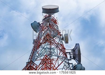 large telecommunication tower against cloudy blue sky