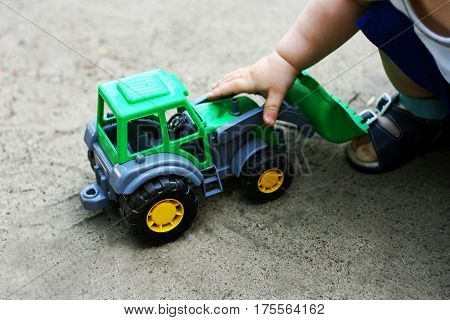 Walks for children in the fresh air. Part of the image of a small child who sits and plays with toy construction vehicles.