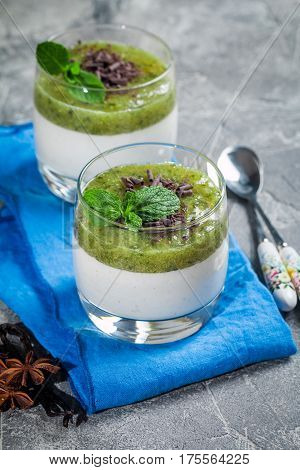 Fruit dessert green panna cotta with mint in a glass over grey background