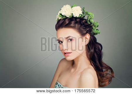 Fashion Model with Prom Hairstyle and Spring Flowers Wreath on Banner Background. Young Woman