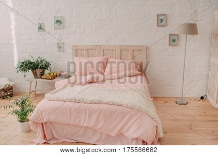 In a bedroom on a large bed of pink bed linens and flowers