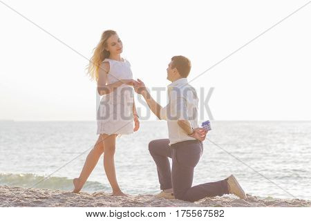 Young Romantic Couple On Seaside At Golden Sunrise. Man Proposes To Girlfriend On The Beach
