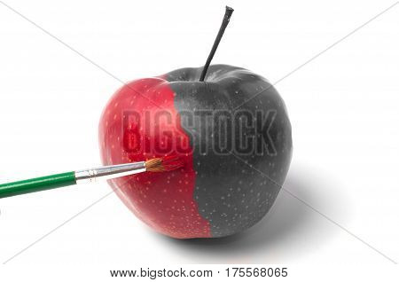 Coloring, drawing on a red apple, using a brush and a paint, partially colorless and colored fresh fruit