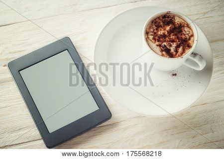 Ebook and a cup of hot cocoa. Flat lay