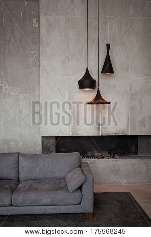 Gray velour sofa in a dark room the bright light from eternal light, and artificial fireplace. Interior loft with concrete walls.