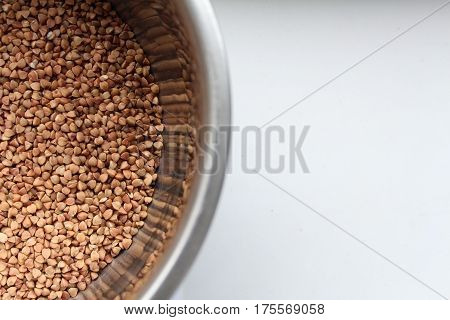 buckwheat in a bowl isolated on white background. free-flowing. buckwheat texture.