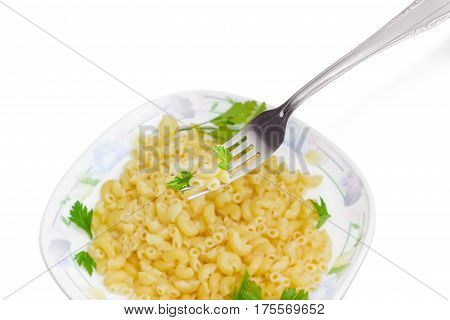 Fragment of the stainless steel fork with some cooked short curved macaroni and the small parsley twigs over of a dish with the same macaroni on a light background