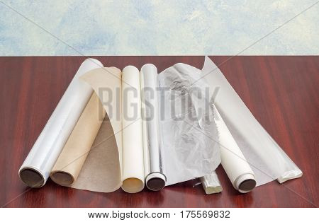 Several rolls of the plastic oven bags plastic food wrap aluminum foil and various parchment paper for household use on a dark red wooden surface
