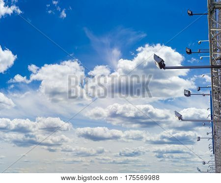 Many light fixtures for billboard backlighting against the background of sky with clouds in daytime