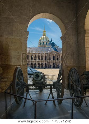 View through the arch to the Honorific Courtyard and a northern facade of the Saint Louis Des Invalides Church with the bronze cannons in the foreground in Paris