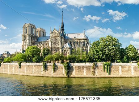 View of the southern facade of the Cathedrale Notre-Dame de Paris from the Seine with the embankment of the river in the foreground against the sky with clouds