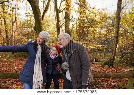 Multi Generation Family Enjoying Walk In Fall Landscape