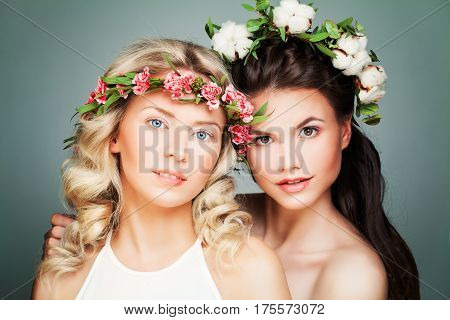 Two Perfect Women Fashion Model with Long Curly Hair and Summer Flowers Wreath. Beauty, Cosmetology and Aesthetic Medicine Concept