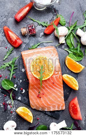 Salmon fillet with fresh ingredients for tasty cooking on rustic background, flat layr. Healthy food concept
