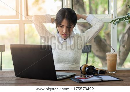 Young Asian woman freelance worker taking a break while working with laptop computer in coffee shop. Startup business and self-employed activity concept