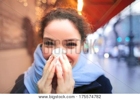 Blowing her nose in a handkerchief