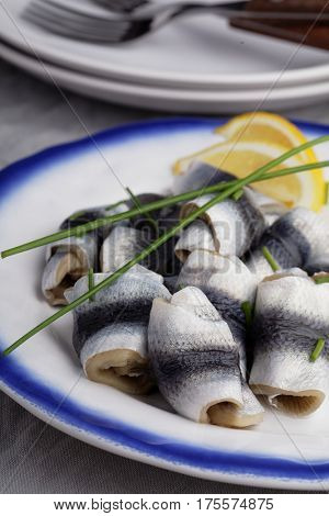 Rollmops the traditional German herring fillet rolls with green onion and lemon in a serving dish