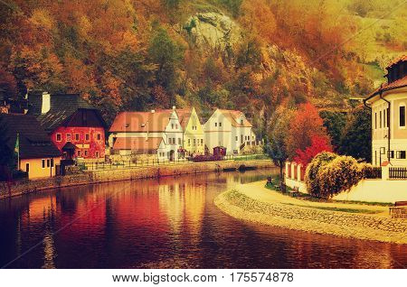 Cesky Krumlov - a famous czech historical beautiful town, view to the city river and beautiful autumn street with colorful buildings and fall trees. Travel european background