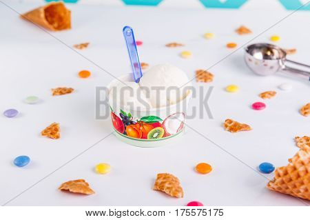 Close Up Vanilla Ice-cream In A Paper Cup On The White Background With Colorful Candies, Pieces Of W