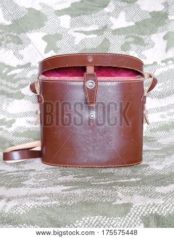 Vintage brown color opened hard leather carry case for binoculars with red cloth inside on camouflage background front view indoor closeup