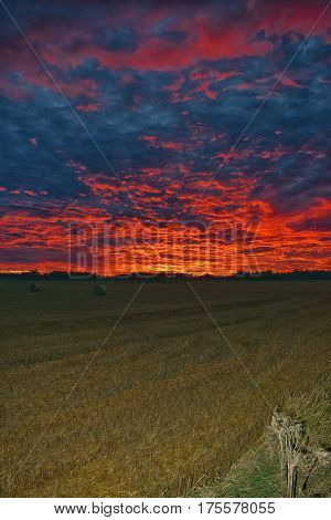 Dramatic sunset over field in Southern Finland. Vertical image.