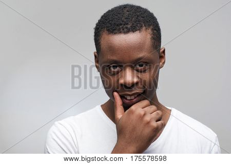 Portrait of young afroamerican man looking at the camera. Cunning, plotting, sly, crafty guy on grey background with free space for text.