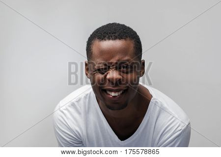 Smiling young african american man winking at the camera. Joy, happiness, laugh, good luck, great mood. Grey background with free space.