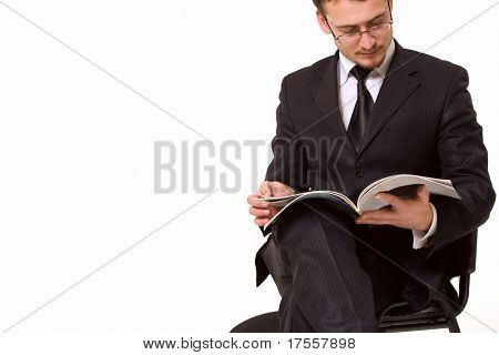 Young handsome man reading magasine. Isolated