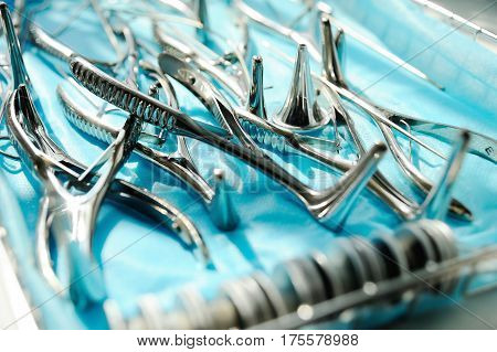 ENT Instruments closeup - nasal mirror, probes, cannulas for washing, nasopharyngeal mirror, ear watering can on a blue background