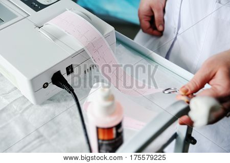Electrocardiogram, ecg in hand. Clinic cardiology heart rhythm and pulse test closeup. Cardiogram printout.