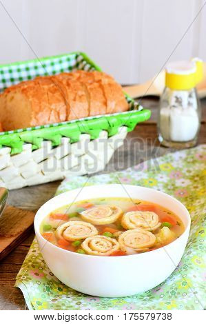 Light vegetable soup with omelet in a bowl, bread slices on a basket. Soup with omelet, carrot, peas, leek, cauliflower and potatoes. Vertical photo. Closeup