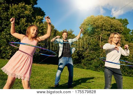Happy family of three playing with hula hoops while enjoying a day in a park together on a sunny summer day