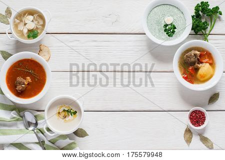 Frame of hot fasting soups on white wood free space. Restaurant serving of lunch dishes menu, flat lay. Buffet, healthy food, warm meal concept